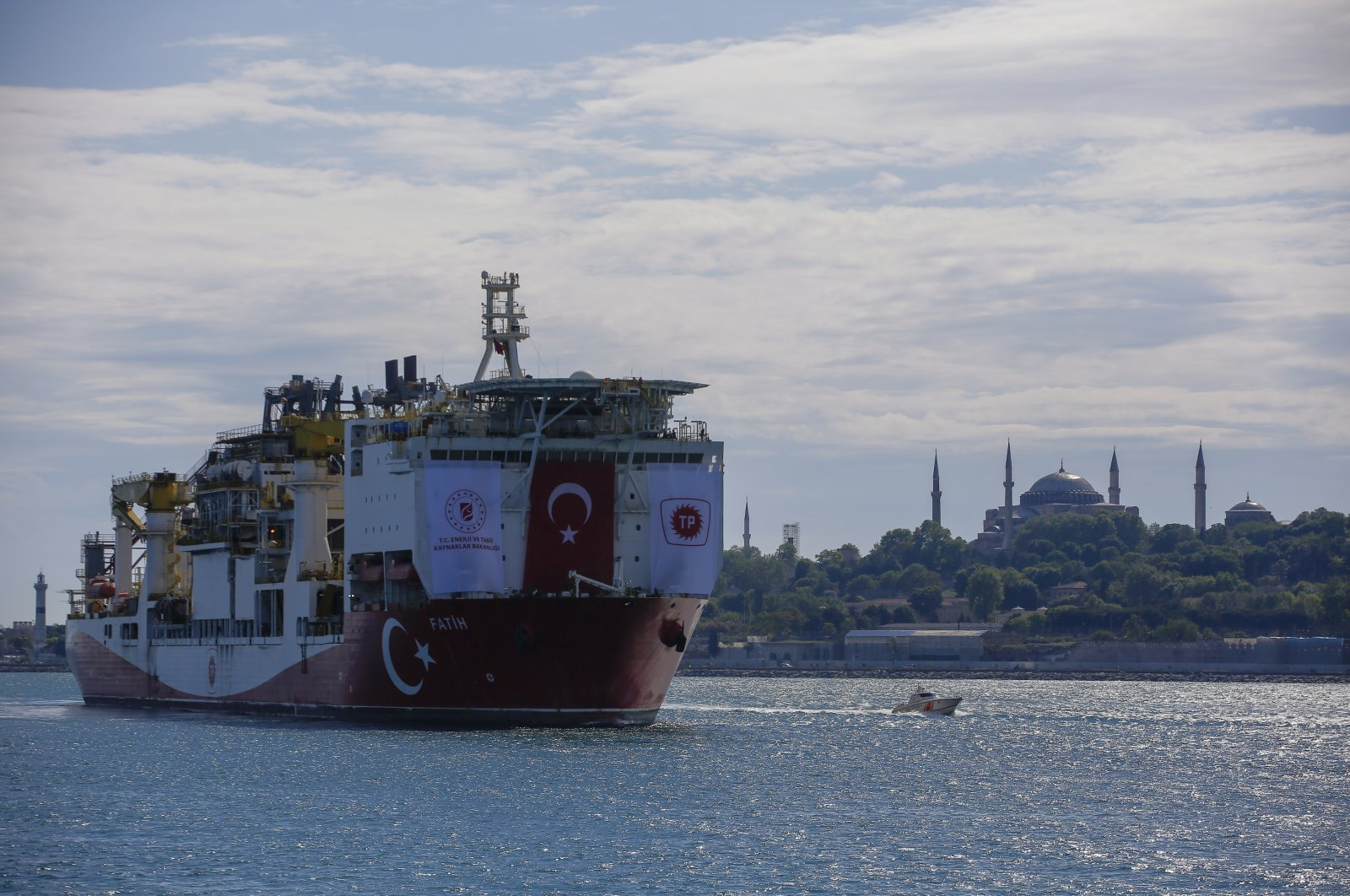 Turkey's drillship, Fatih, crosses the Bosporus as it heads toward the Black Sea with the Hagia Sophia Grand Mosque in the background, Istanbul, May. 29, 2020. (AP Photo)