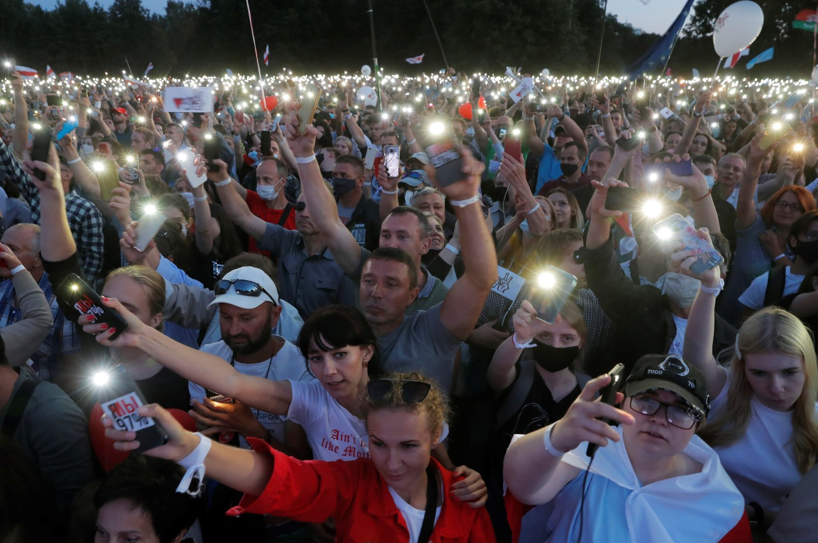 Supporters of Belarusian presidential candidate Svetlana Tikhanovskaya use the flashlights on their phones to express support during an election campaign rally in Minsk, Belarus, July 30, 2020. (Reuters Photo)