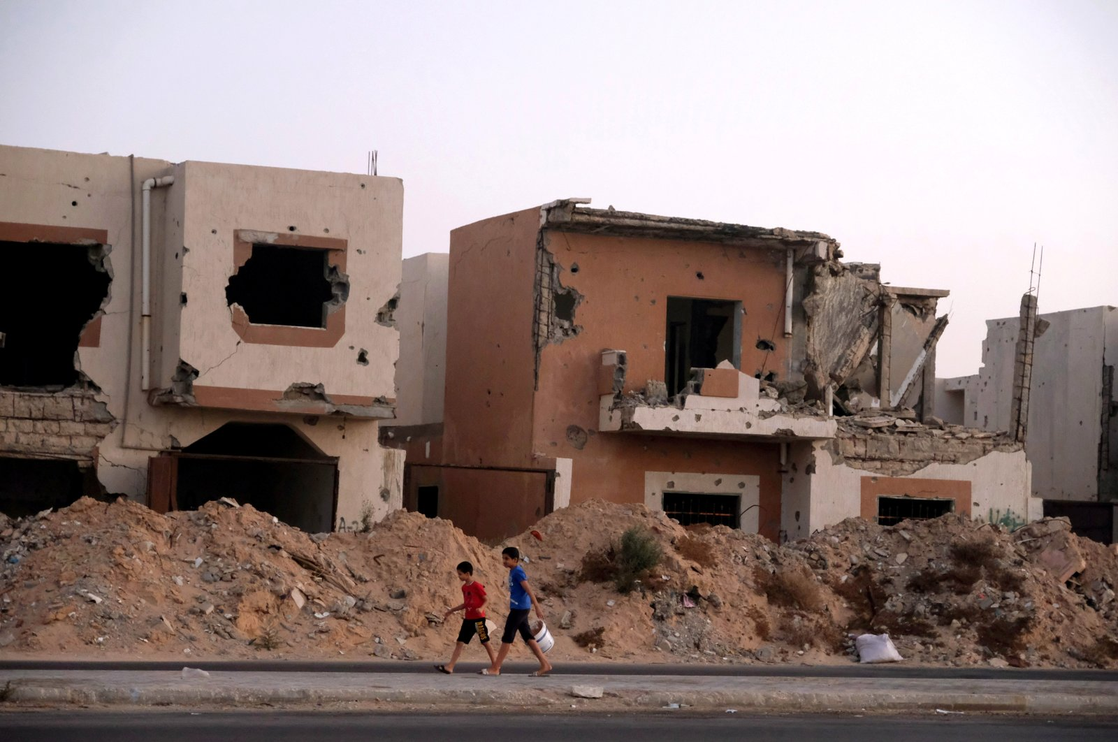 Boys walk past houses that were destroyed in past fighting with Daesh militants in Sirte, Libya, Aug. 17, 2020. (REUTERS Photo)