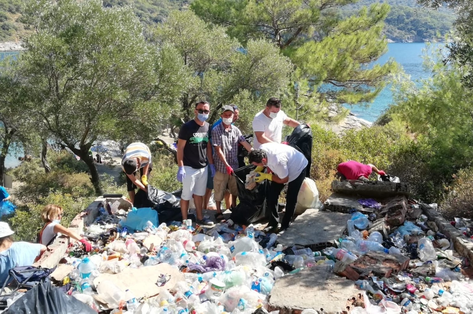 Volunteers stand beside a pile of collected garbage in Darboğaz Bay, in the Fethiye district of Muğla province, southwestern Turkey, Aug. 23, 2020. (AA Photo)