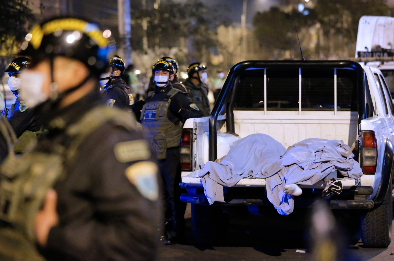 The bodies of some of the victims that suffocated in a crush during a raid on a nightclub in Lima, Peru, are seen on the back of a pickup truck outside the place where a party was being held despite a ban on such gatherings imposed to fight the coronavirus pandemic, Aug. 23, 2020. (AFP Photo)