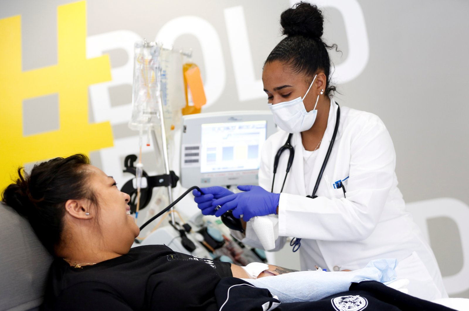 Phlebotomist Jenee Wilson talks with Melissa Cruz, an ER technician for Valley Medical Center, as she finishes donating convalescent plasma at the Central Seattle Donor Center of Bloodworks Northwest during the coronavirus outbreak in Seattle, Washington, U.S., April 17, 2020. (Reuters Photo)