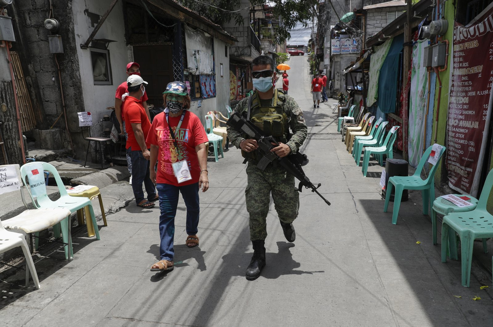An army soldier walks with a volunteer as they wait for relief goods to be distributed and placed on chairs outside homes during a continuing enhanced community quarantine to prevent the spread of the coronavirus in Quezon City, Metro Manila, Philippines, May 4, 2020. (AP Photo)
