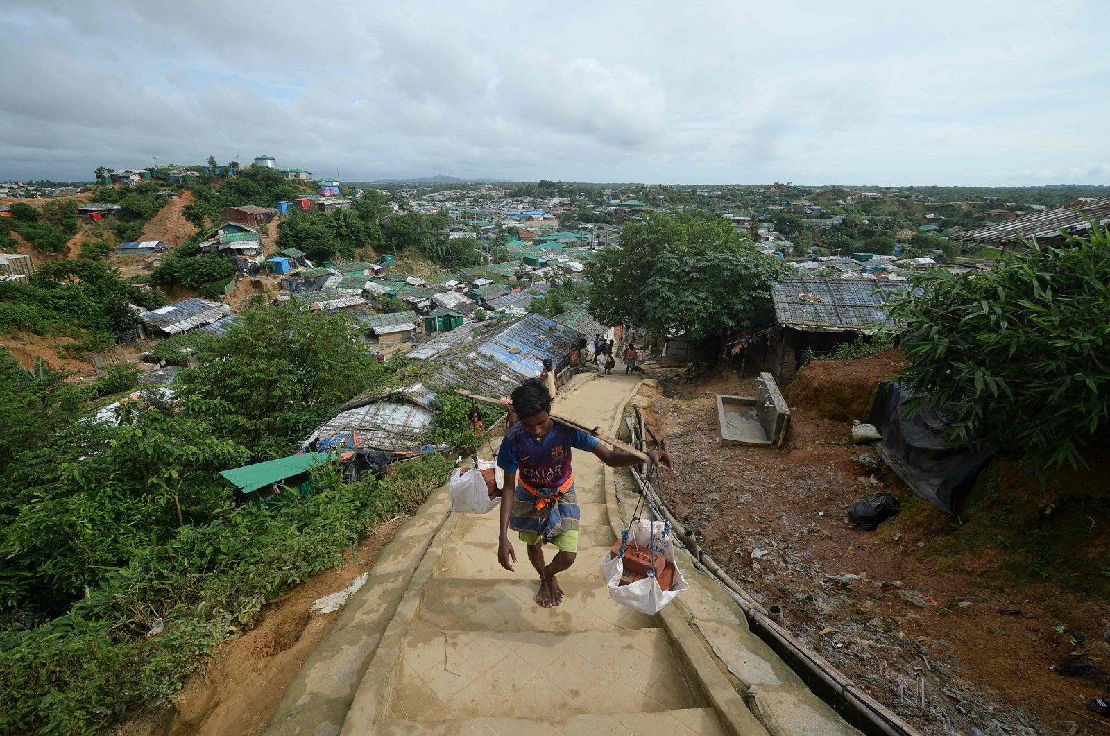 A Rohingya man carries bricks up a hill for construction works in a Jamtoli refugee camp near Ukhia, Bangladesh, Aug. 23, 2020. (AFP Photo)