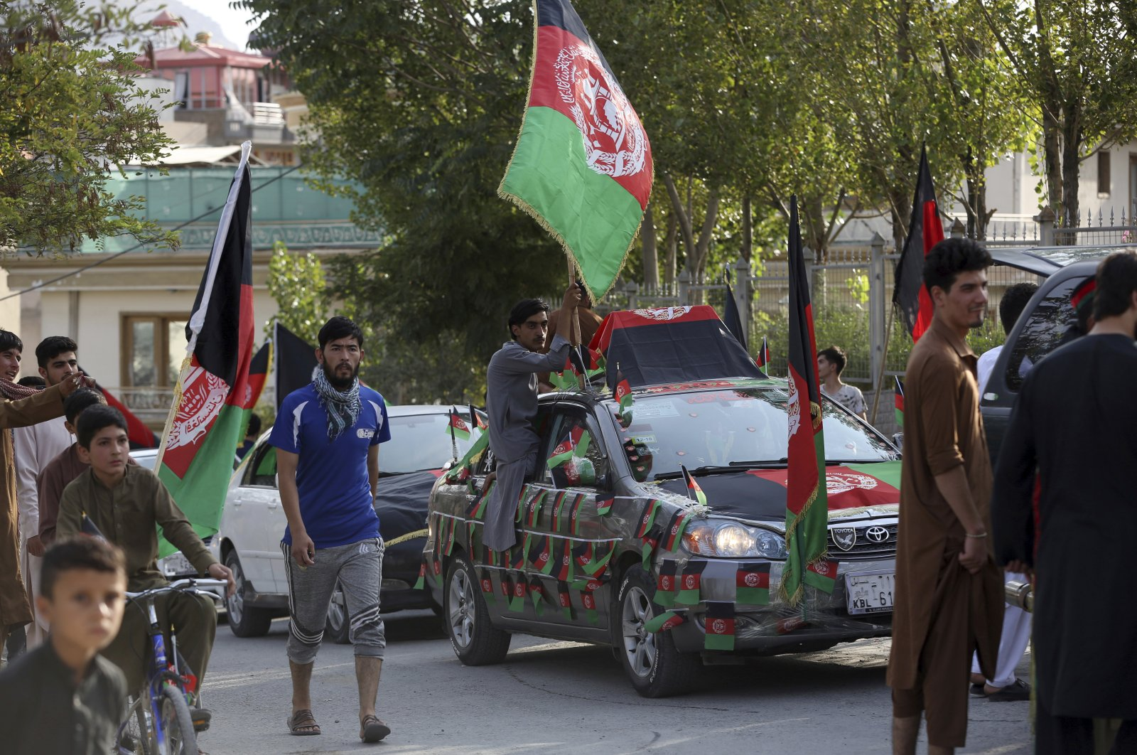 Afghans cover their cars with the Afghan National flag during the Independence Day celebrations in Kabul, Afghanistan, Aug. 18, 2020. (AP Photo)