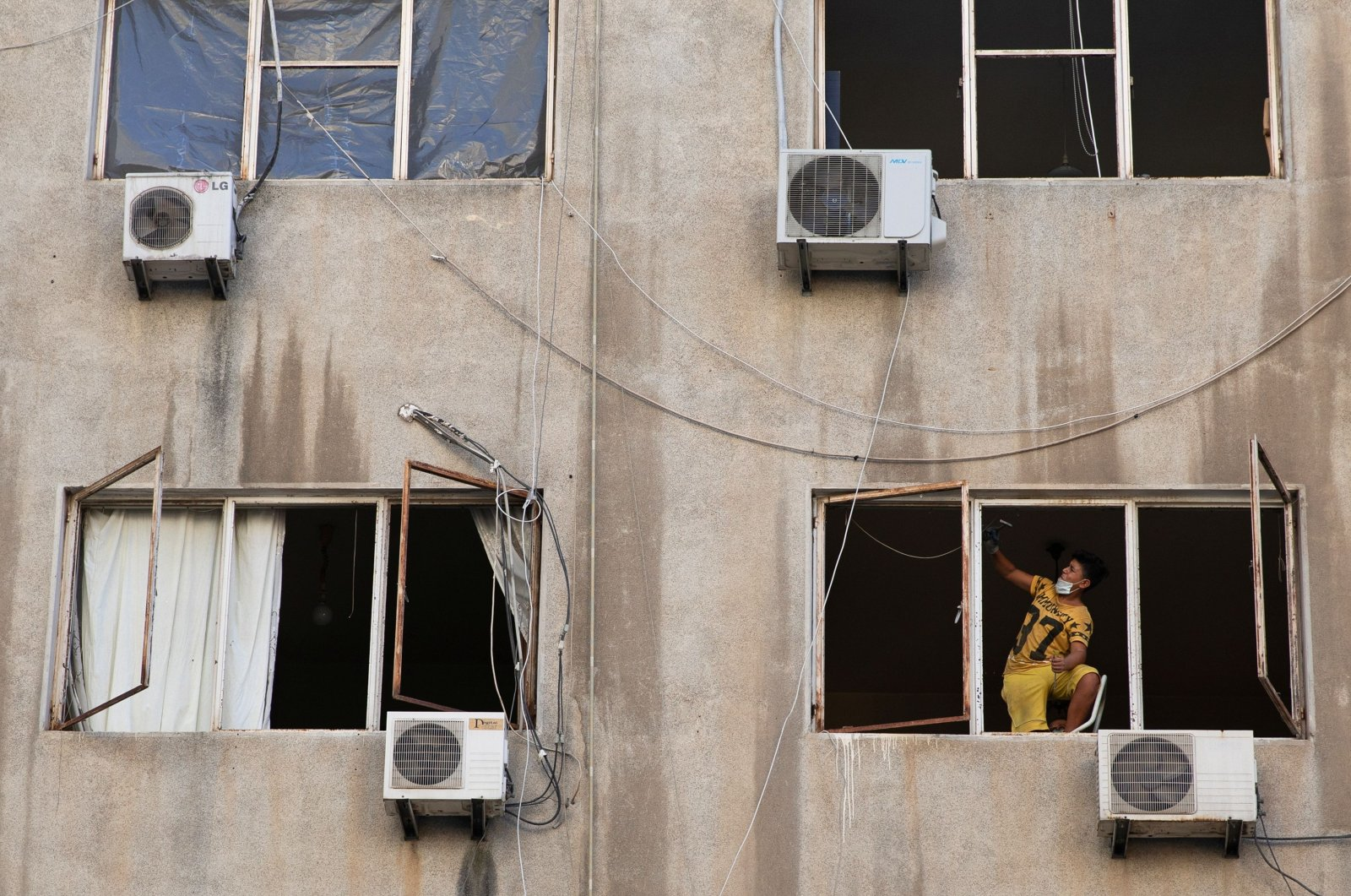 A boy fixes a damaged window in the aftermath of a massive explosion at the port area, Beirut, Aug. 17, 2020. (REUTERS Photo)
