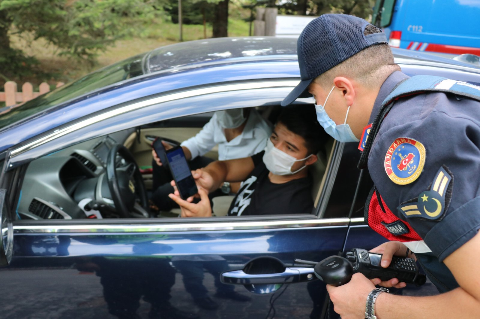 A gendarmerie officer checks a visitor's HES code at the entrance of a national park, in Bolu, northern Turkey, Aug. 23, 2020. (İHA Photo)