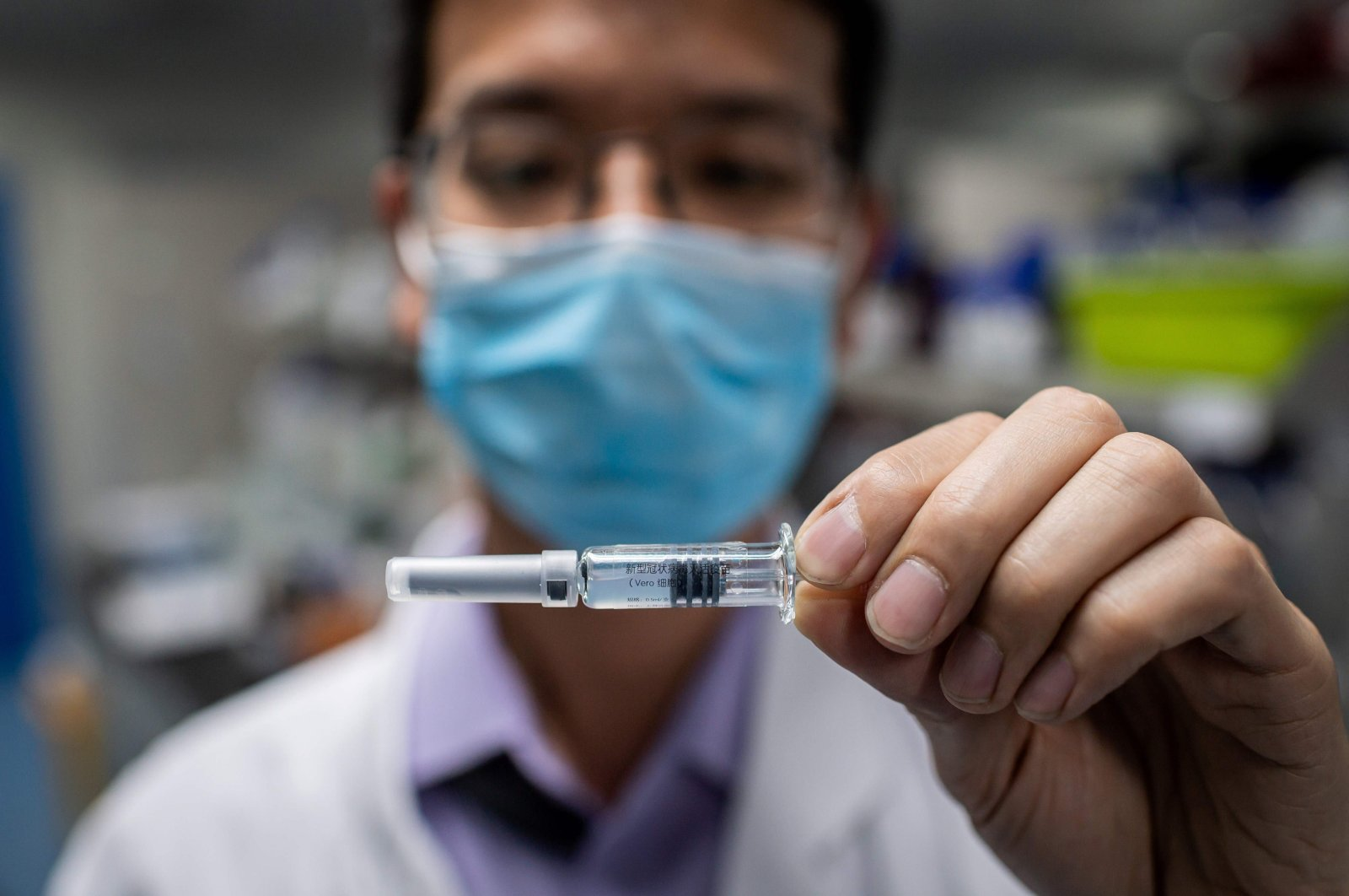 An engineer shows an experimental vaccine for COVID-19 that was tested at the Quality Control Laboratory at the Sinovac Biotech facilities, Beijing. Apr. 29, 2020. (AFP Photo)