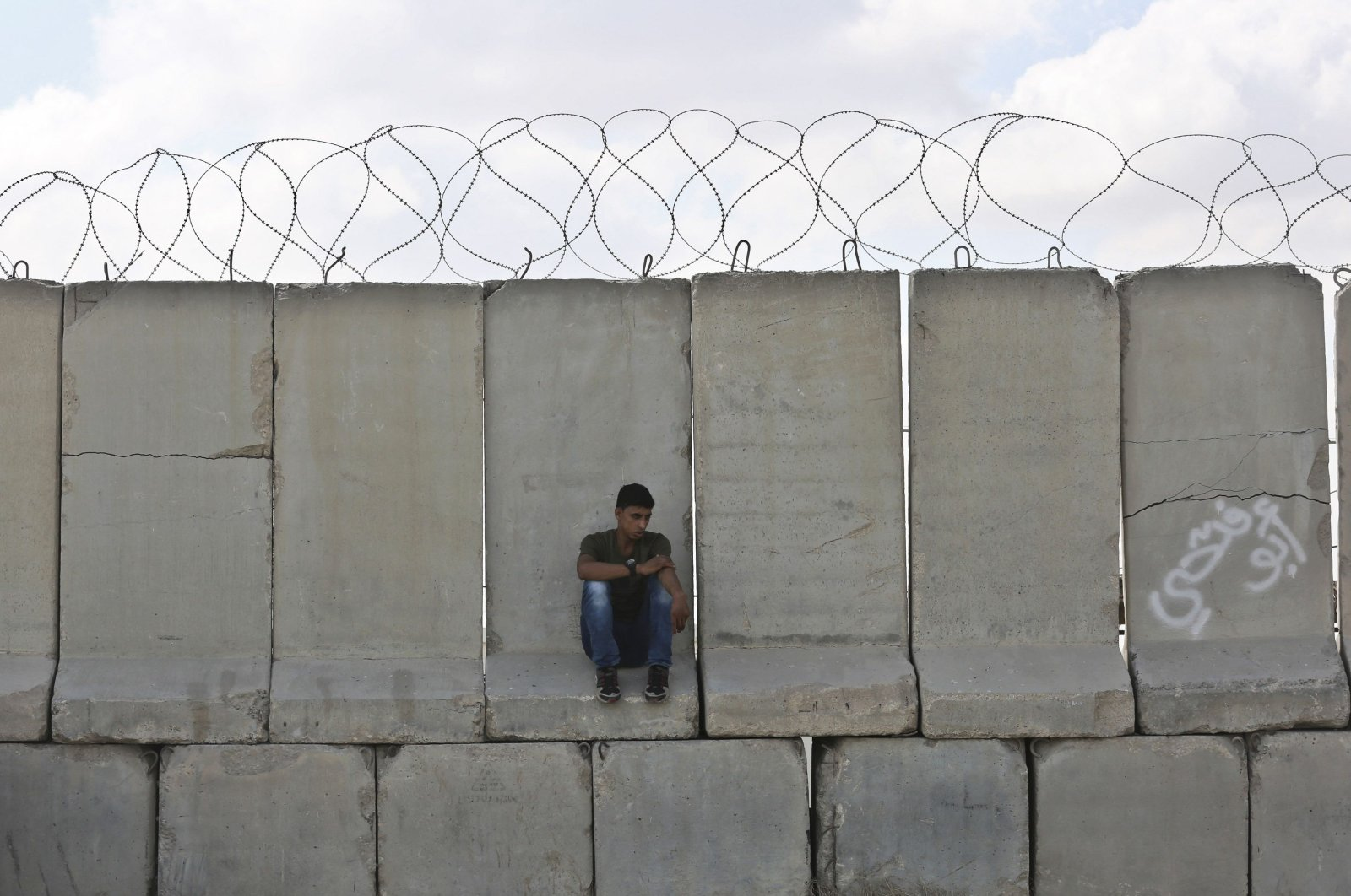 A Palestinian man sits on cement barricades at Kerem Shalom crossing, Rafah, Aug. 15, 2018. (AFP Photo)