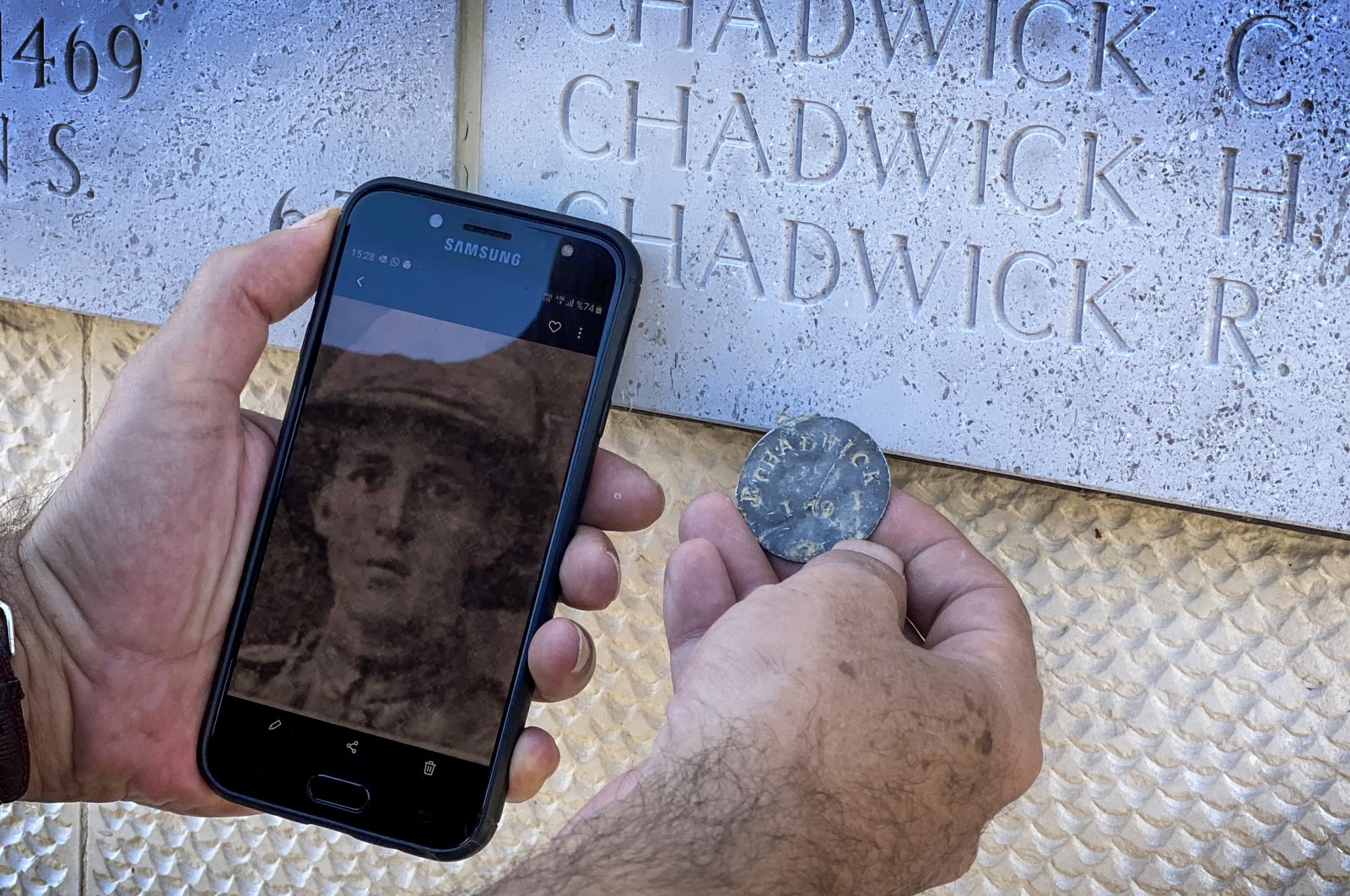 Seyit Ahmet Sılay shows the dog tag and photo of British soldier Robert Chadwick in front of a monument with the name of the soldier inscribed on it, in Çanakkale, western Turkey, Aug. 24, 2020. (AA Photo)
