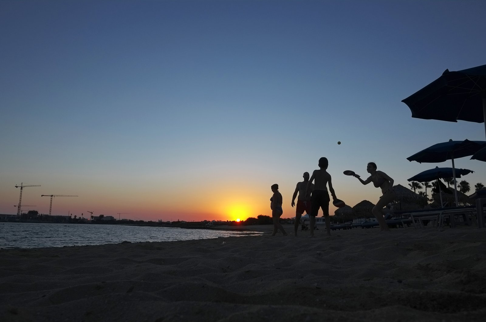 People play racketball at the beach during sunset in the coastal resort of Ayia Napa on the Greek side of the Eastern Mediterranean island of Cyprus, Aug. 22, 2020. (AP Photo)