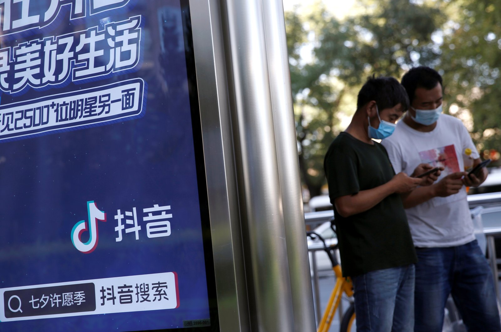People wearing face masks during the coronavirus outbreak use smartphones next to an advertisement for TikTok at a bus stop in Beijing, China, Aug. 24, 2020. (Reuters Photo)