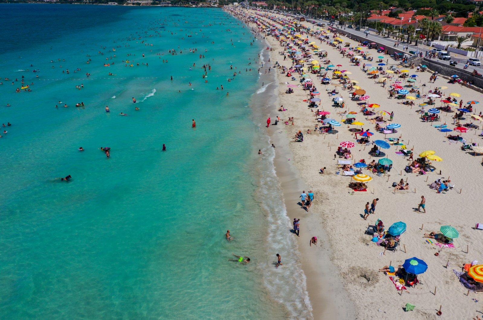 People are seen at Ilıca Beach in Çeşme, a resort town west of Izmir, in Turkey's Aegean region, July 19, 2020. (AA Photo)