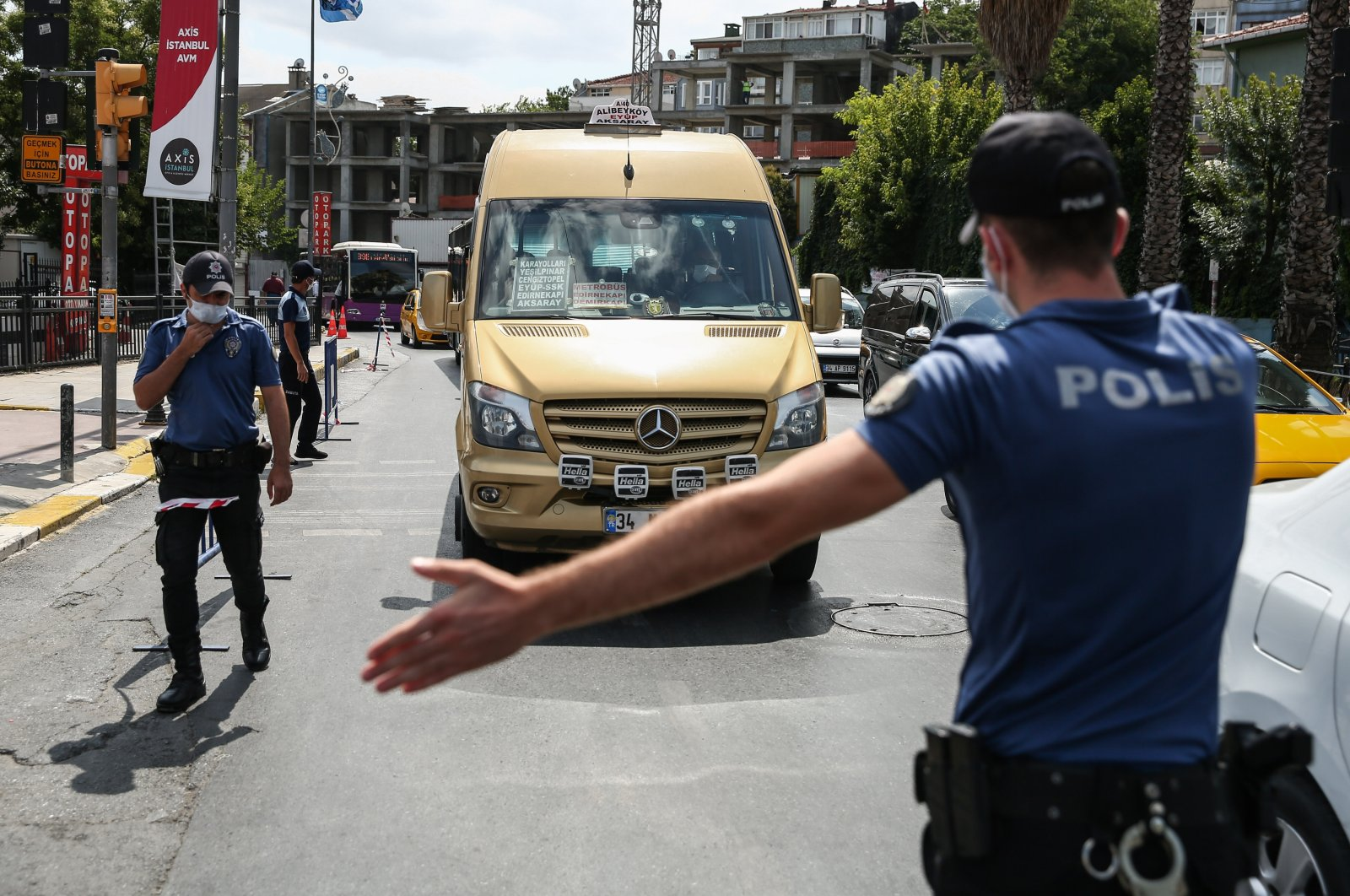A police officer motions for a minibus to pull over to inspect for COVID-19 precautions, Istanbul, Turkey, Aug. 6, 2020. (DHA Photo)