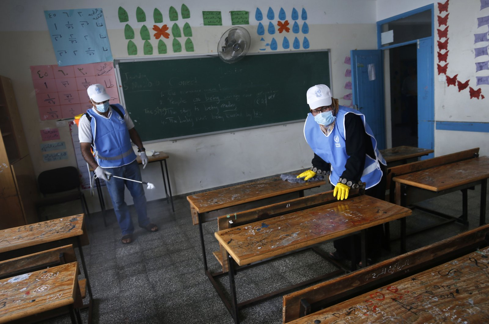 Palestinian workers wearing protective face masks sanitises a classroom in a United Nations-run school before a new academic year starts, amid concerns about the spread of COVID-19, in Gaza City, Aug. 5, 2020. (AFP Photo)