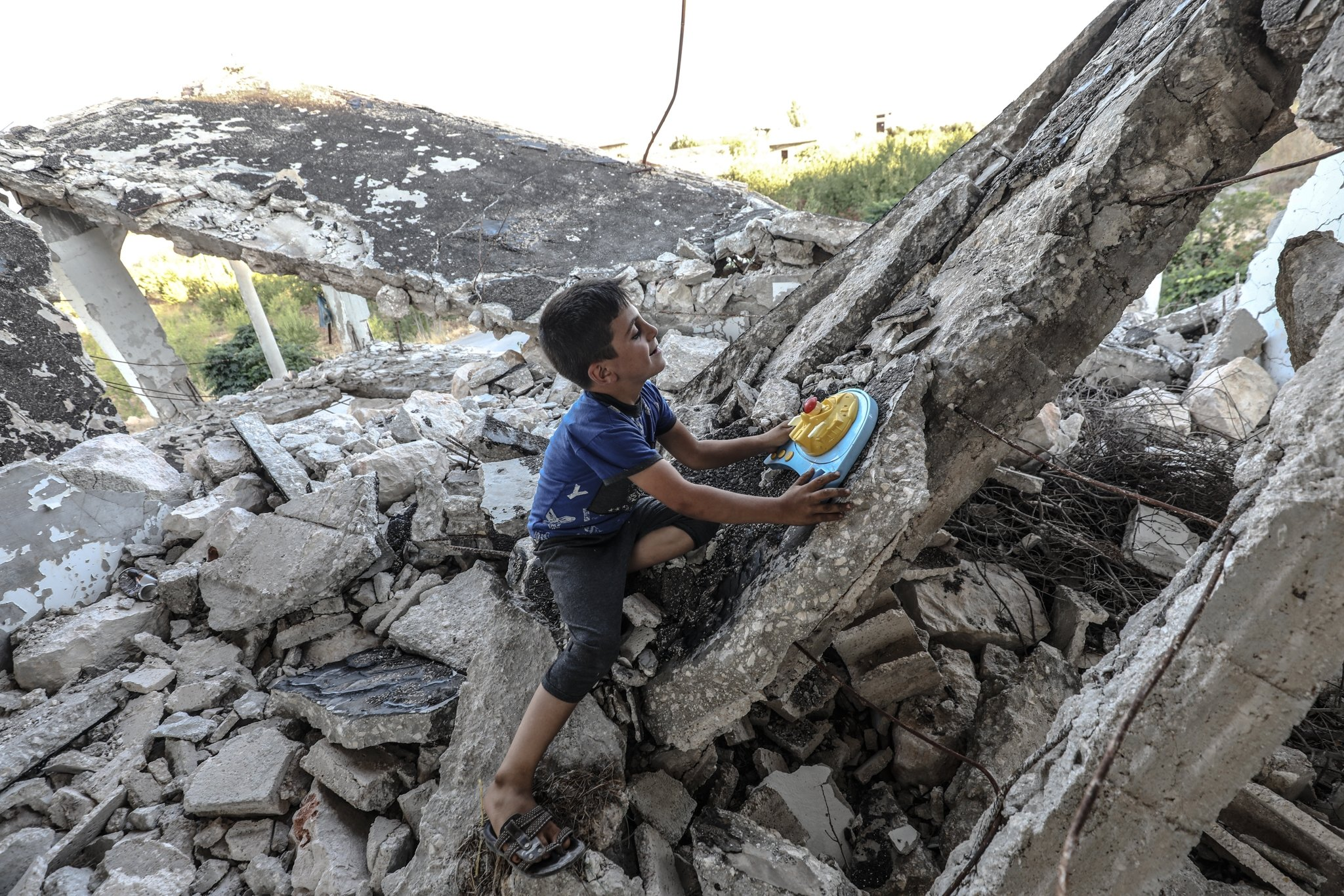 7-years-old Mohamad plays in his wrecked home damaged by Syrian regime attacks, Aug. 25, 2020. (AA)
