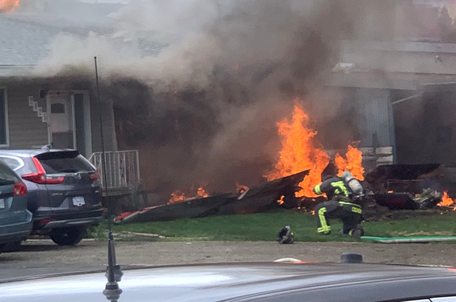 This image obtained from social media shows the crash site of a jet from the Canadian air force's Snowbirds aerobatics team is seen in a residential neighborhood in Kamloops, British Columbia, Canada, May 17, 2020. (Courtesy of Elwood Delaney/via Reuters)