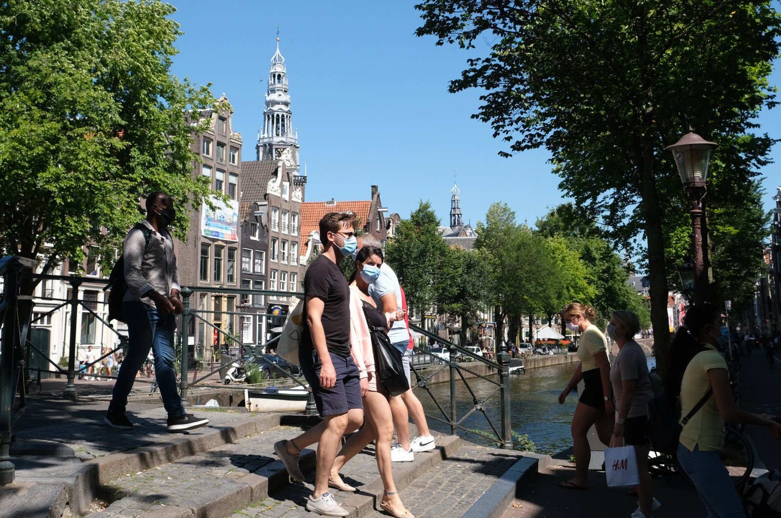 People wearing face masks to prevent the spread of the coronavirus walk through Amsterdam, the Netherlands, Aug. 5, 2020. (AP Photo)