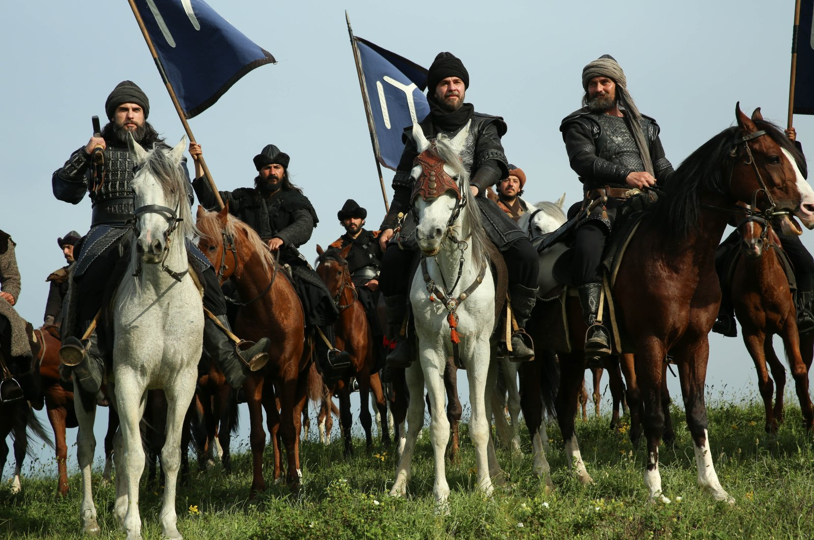 """A still shot from the Turkish series """"Resurrection: Ertuğrul"""" depicting Ertuğrul (C) and other Turkish heroes (Alps) riding horses and holding the iconic flag of the Kayı tribe."""