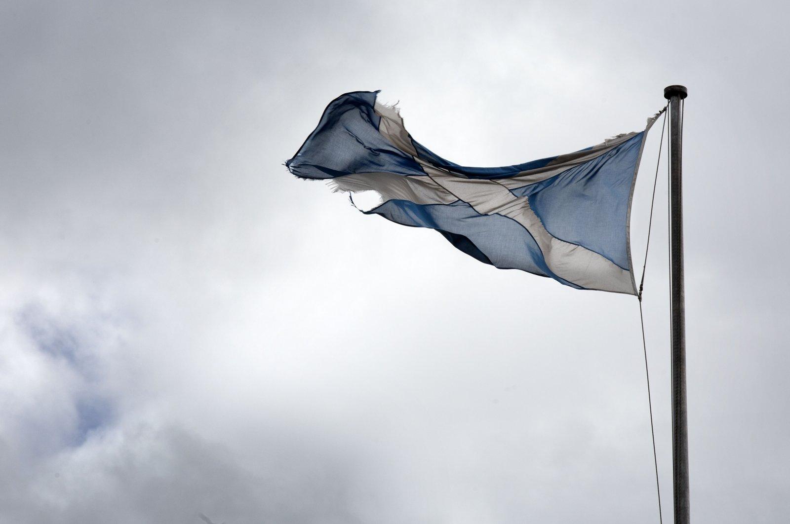 A torn Scottish Saltire flag hangs over the Royal Mile in Edinburgh, Scotland, Aug. 21, 2020. (AP Photo)