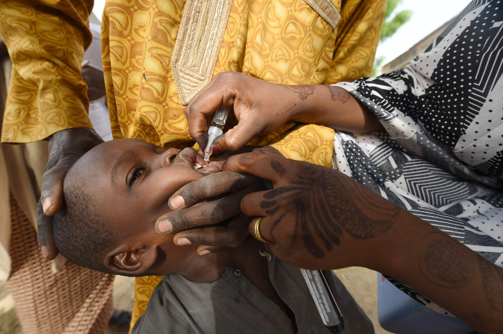 In this file photo taken on April 22, 2017, a health worker administers a vaccine to a child during a vaccination campaign against polio at Hotoro-Kudu, in the Nassarawa district of Kano, northwest Nigeria. (AFP Photo)