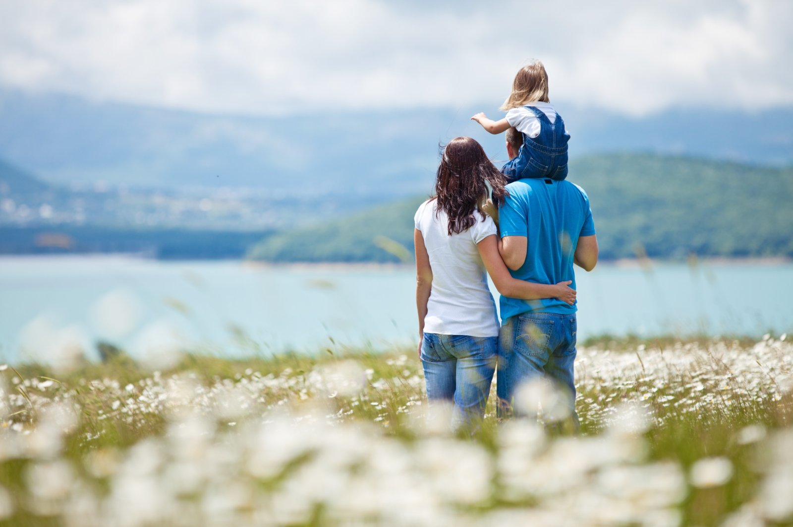 A family standing in front of a lake watches nature (Shutterstock Photo)