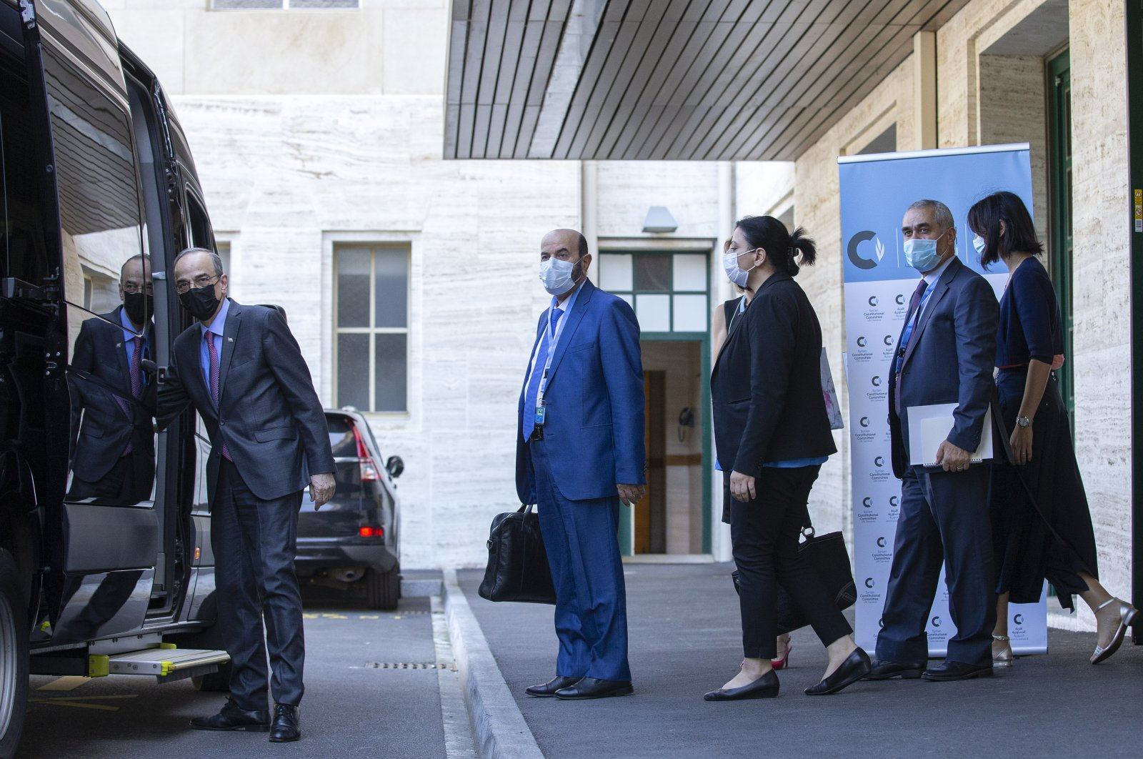 Syrian Constitutional Committee Co-Chair Hadi al-Bahra (L) leaves following the announcement of the suspension of the conference due to cases of COVID-19, at the European headquarters of the United Nations in Geneva, Switzerland, Aug. 24, 2020. (AP Photo)