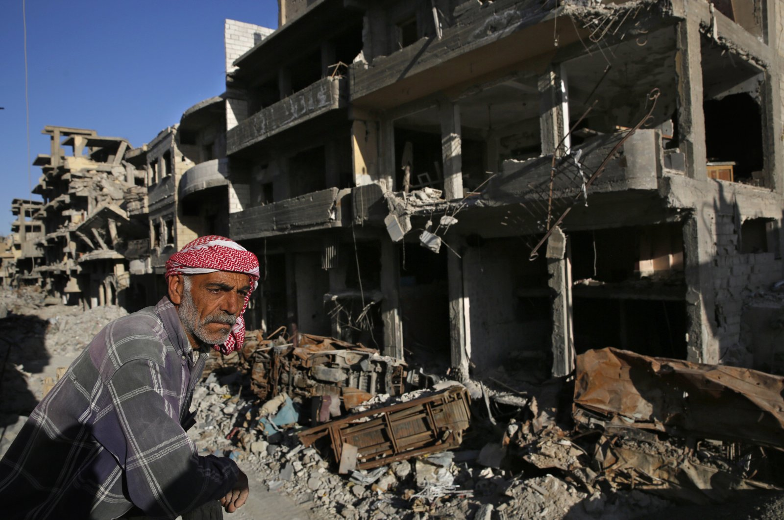 A Syrian man stands between buildings destroyed during the fighting against Daesh militants in Raqqa, April 5, 2018. (AP Photo)