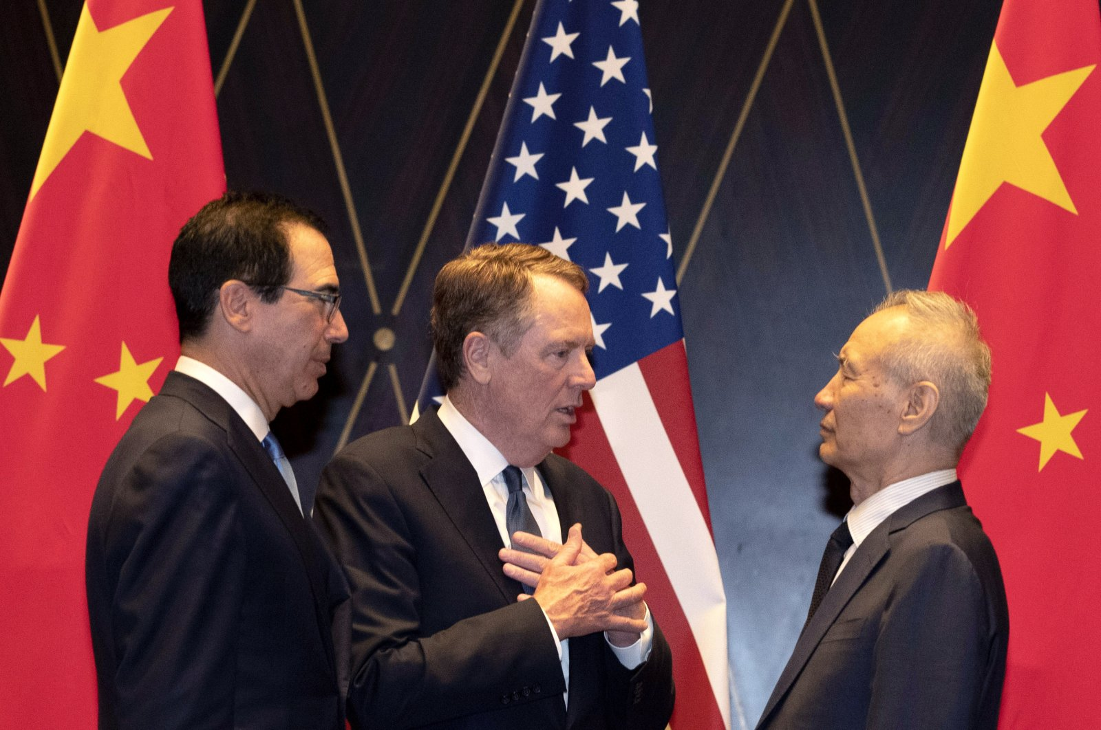 U.S. Trade Representative Robert Lighthizer (C), gestures as he chats with Chinese Vice Premier Liu He (R) with Treasury Secretary Steven Mnuchin (L), looking on after posing for a family photo at the Xijiao Conference Center in Shanghai, July 31, 2019. (AP Photo)