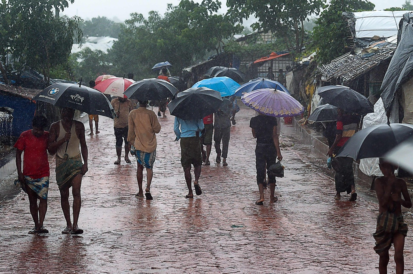 Rohingya people make their way during a monsoon rain in Kutupalong refugee camp in Ukhia on Aug.25, 2020. (AFP File Photo)