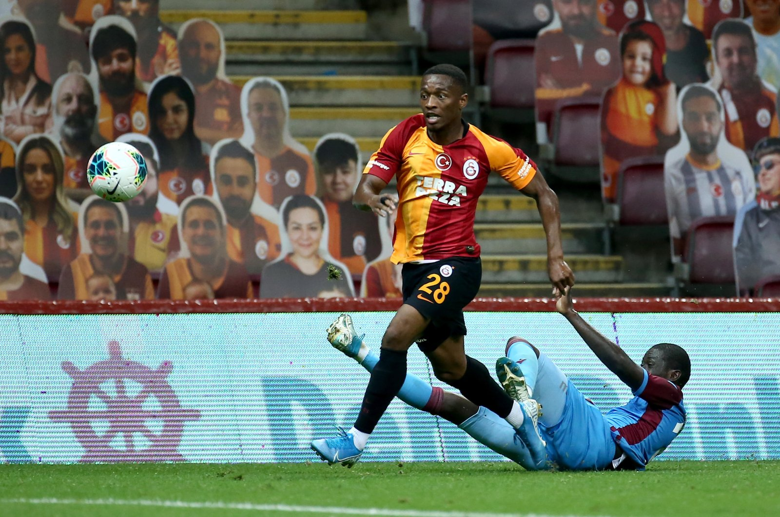 Fans' cut-outs appear in the background as Galatasaray's Jesse Sekidika (L) goes past Trabzonspor's Badou Ndiaye during a Turkish Süper Lig at the Türk Telekom Stadium, Istanbul, July 7, 2020 (AA Photo)