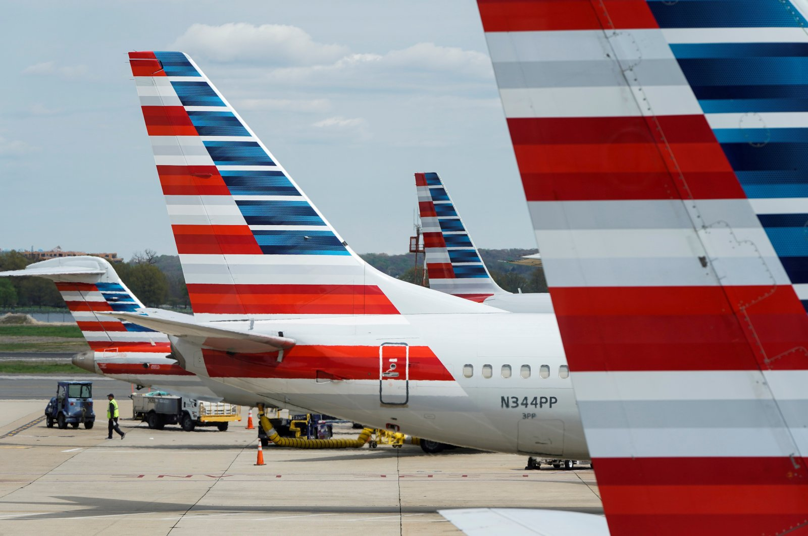 A member of a ground crew walks past American Airlines planes parked at the gate during the coronavirus disease (COVID-19) outbreak at Ronald Reagan National Airport in Washington, U.S., April 5, 2020. (Reuters Photo)