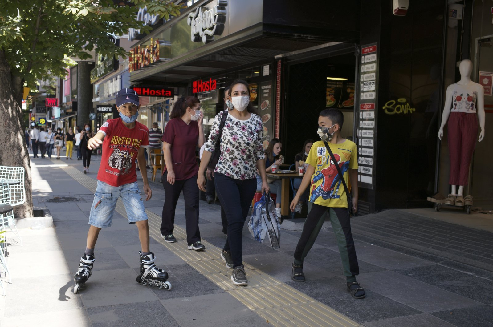 People wearing face masks to protect against the spread of coronavirus, walk in Ankara, Turkey, Wednesday, Aug. 5, 2020. (AP Photo)