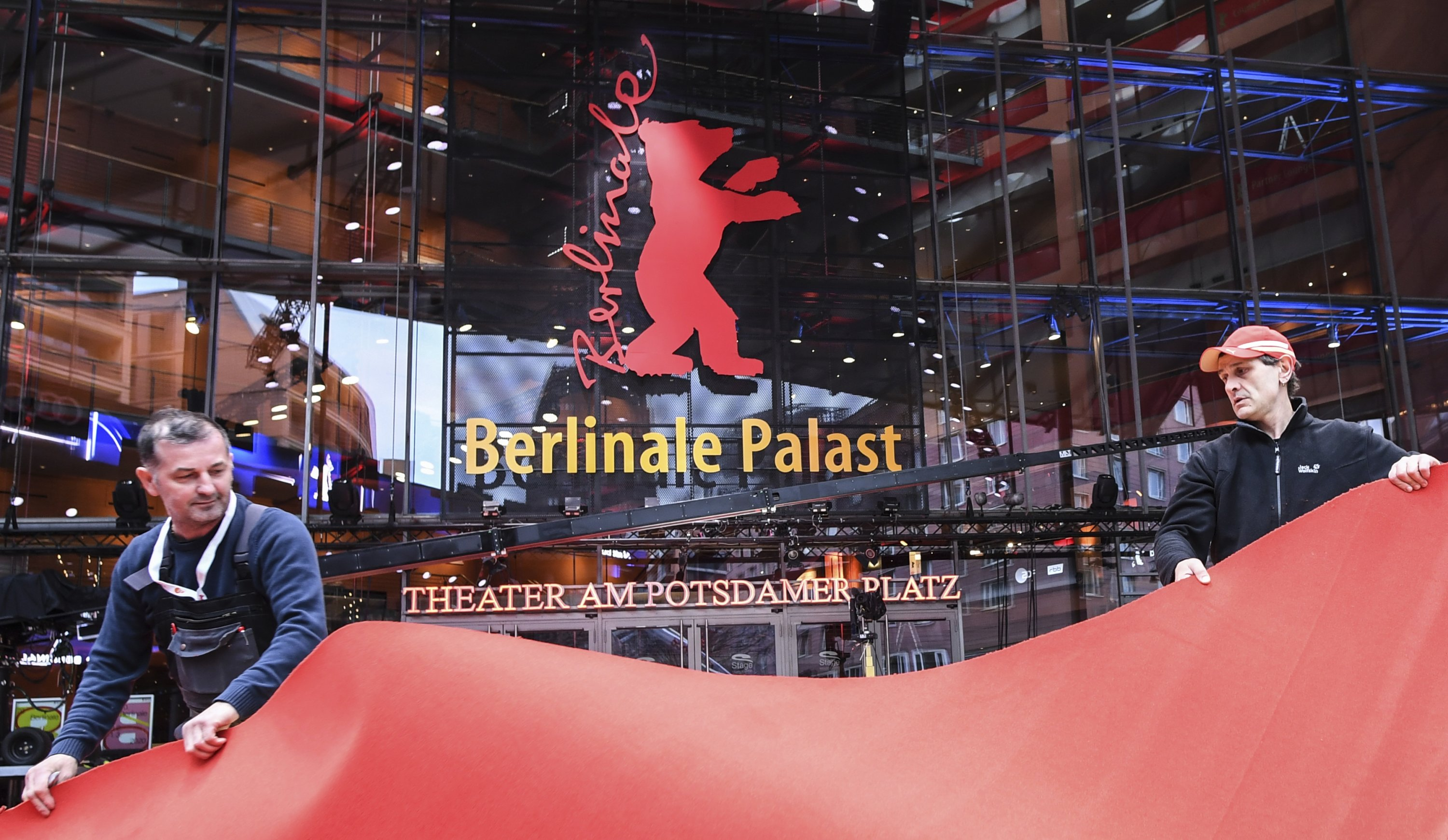 Workers roll out the carpet for the 70th edition of the Berlin International Film Festival, in Berlin, Germany on Feb. 18, 2020. (AP Photo)