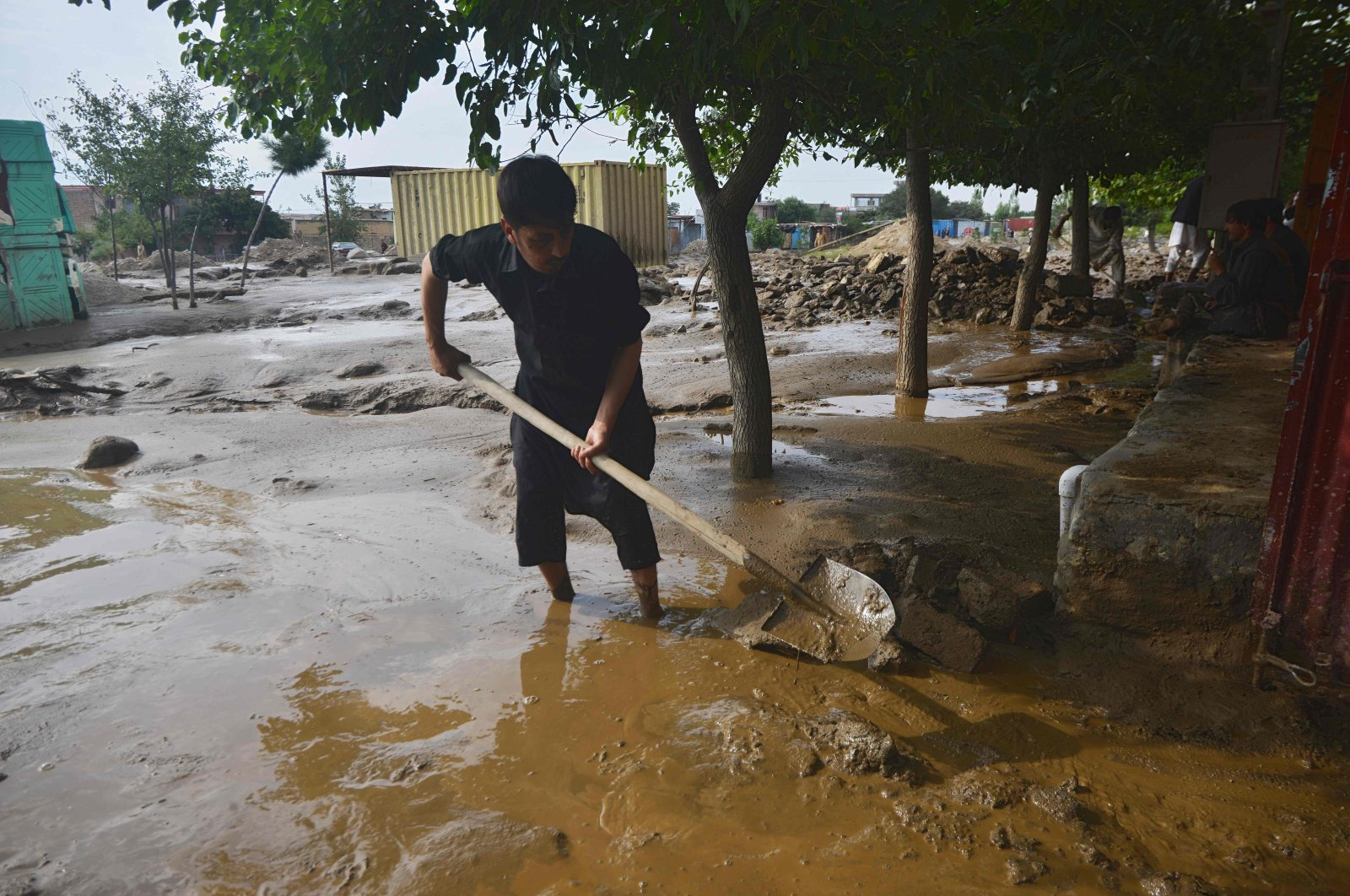 A flash flood-affected villager uses a shovel to clear the mud after heavy rains at Charikar in Parwan province on Aug. 26, 2020. (AFP Photo)