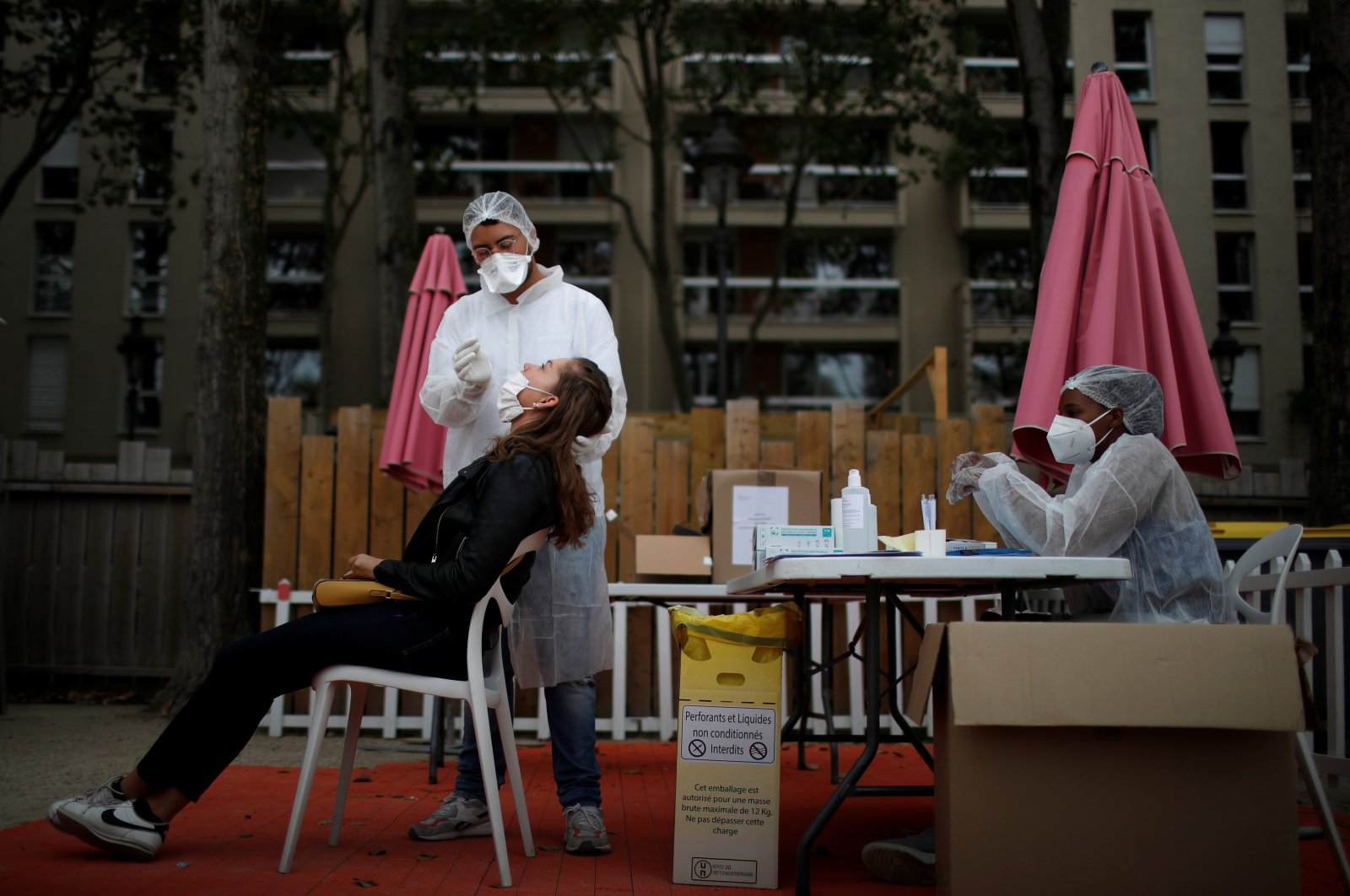 A health worker wearing a protective suit and a face mask administers a nasal swab to a patient at a testing site at the Bassin de la Villette, Paris, France, Aug. 25, 2020. (Reuters Photo)