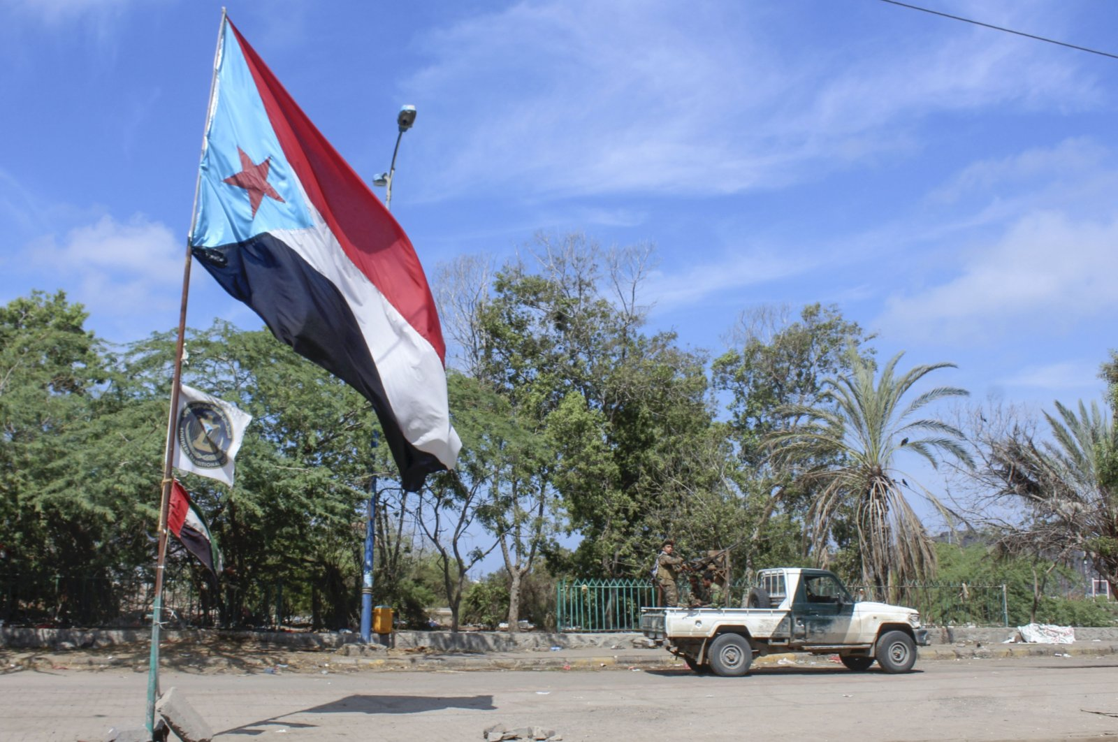 Fighters with Yemen's Southern Transitional Council (STC) drive a vehicle past a separatist flag (the old flag of South Yemen) as they deploy in the southern city of Aden, April 26, 2020. (AFP Photo)