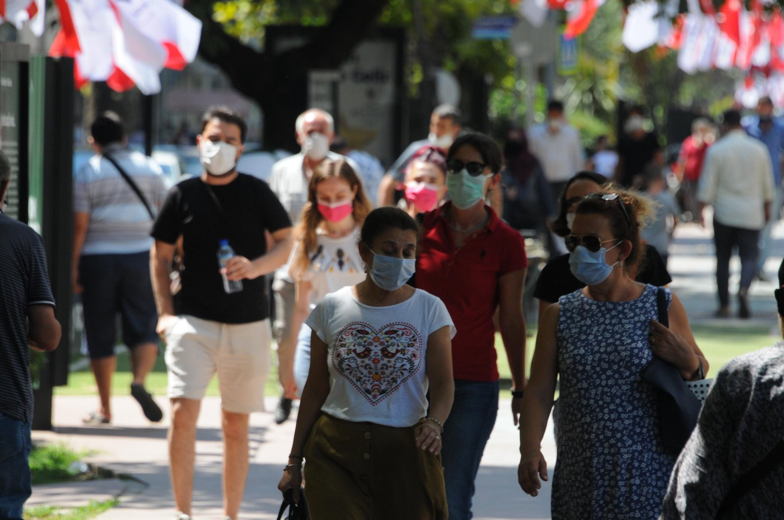 People wearing protective masks against the coronavirus walk on a street in Kocaeli province, northwestern Turkey, Aug. 26, 2020. (DHA Photo)