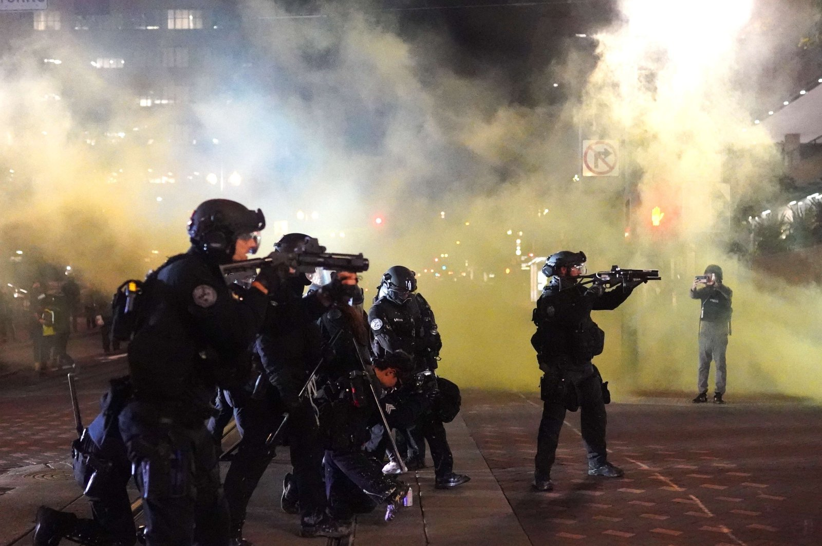 Portland police officers fire nonlethal rounds through smoke while dispersing protesters from Portland City Hall, Portland, Oregon, Aug. 25, 2020. (AFP Photo)
