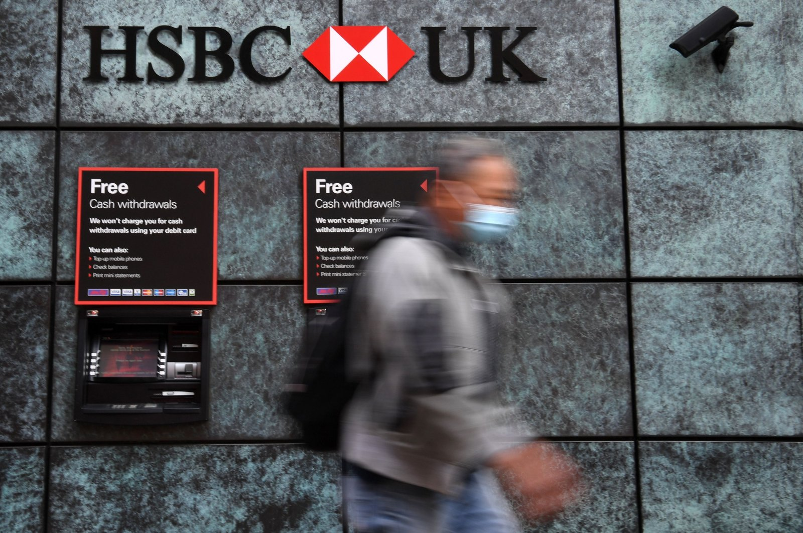 A pedestrian wearing a face mask or covering due to the COVID-19 pandemic walks past a branch of an HSBC bank in central London, Britain, Aug. 3, 2020. (AFP Photo)