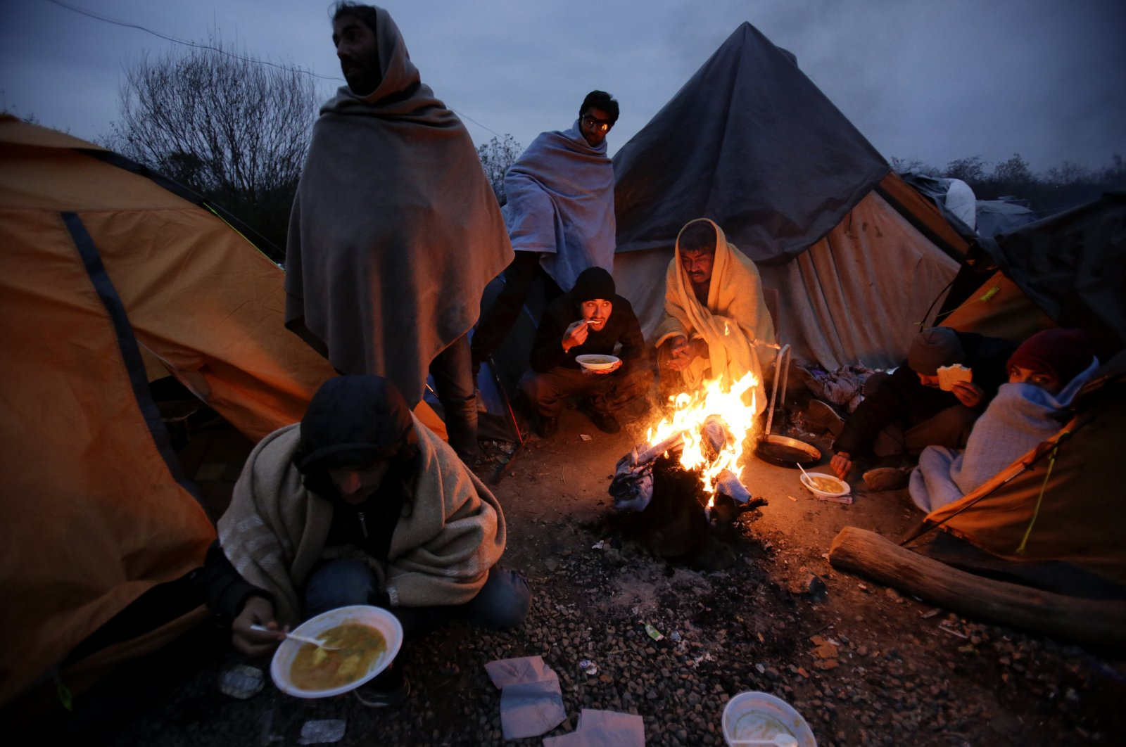Migrants eat around a fire at a camp in Velika Kadusa, Bosnia-Herzegovina, close to the border with Croatia, Nov. 18, 2019. (AP Photo)
