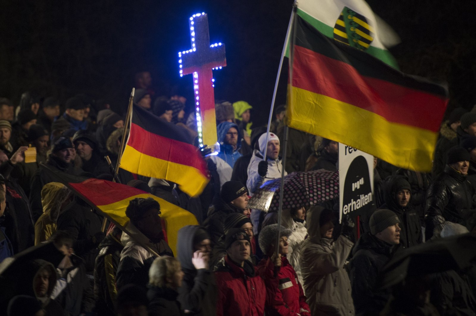 A demonstrator holds a crucifix in the colors of Germany during a rally by a mounting right-wing populist movement called PEGIDA on Jan. 5, 2015, in Dresden. (AFP Photo)