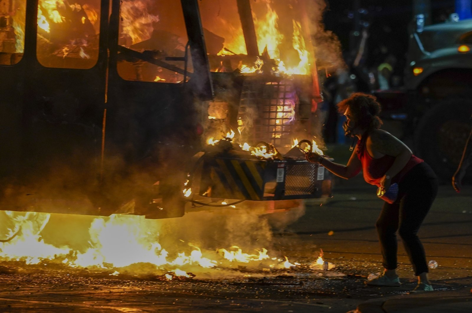 A protester lights a cigarette on a garbage truck that was set on fire during protests in Kenosha, Aug. 24, 2020.(AP Photo)