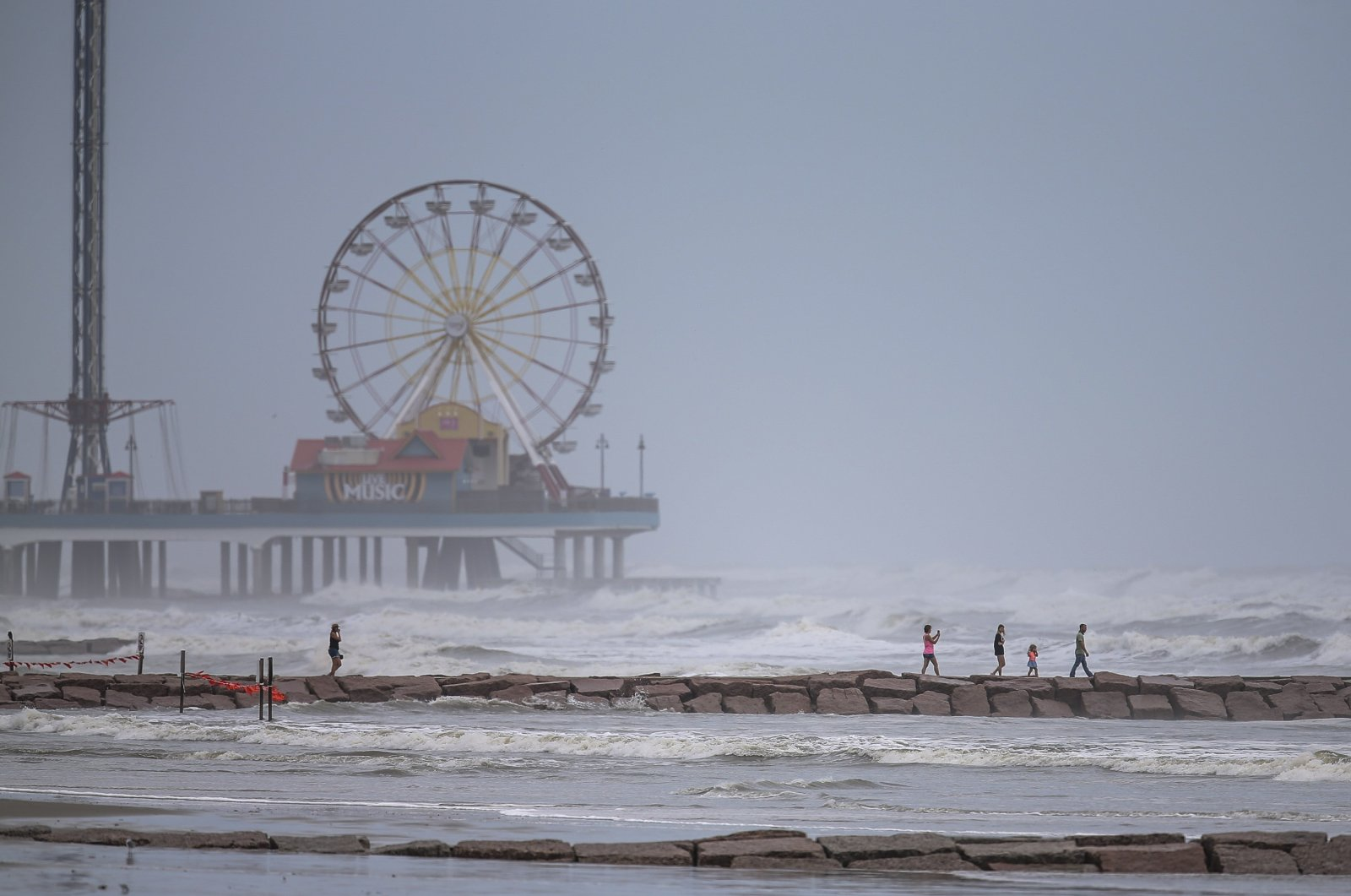 People walk along a jetty as waves roll in from approaching Hurricane Laura in Galveston, Texas,  Aug. 25, 2020. (AFP Photo)