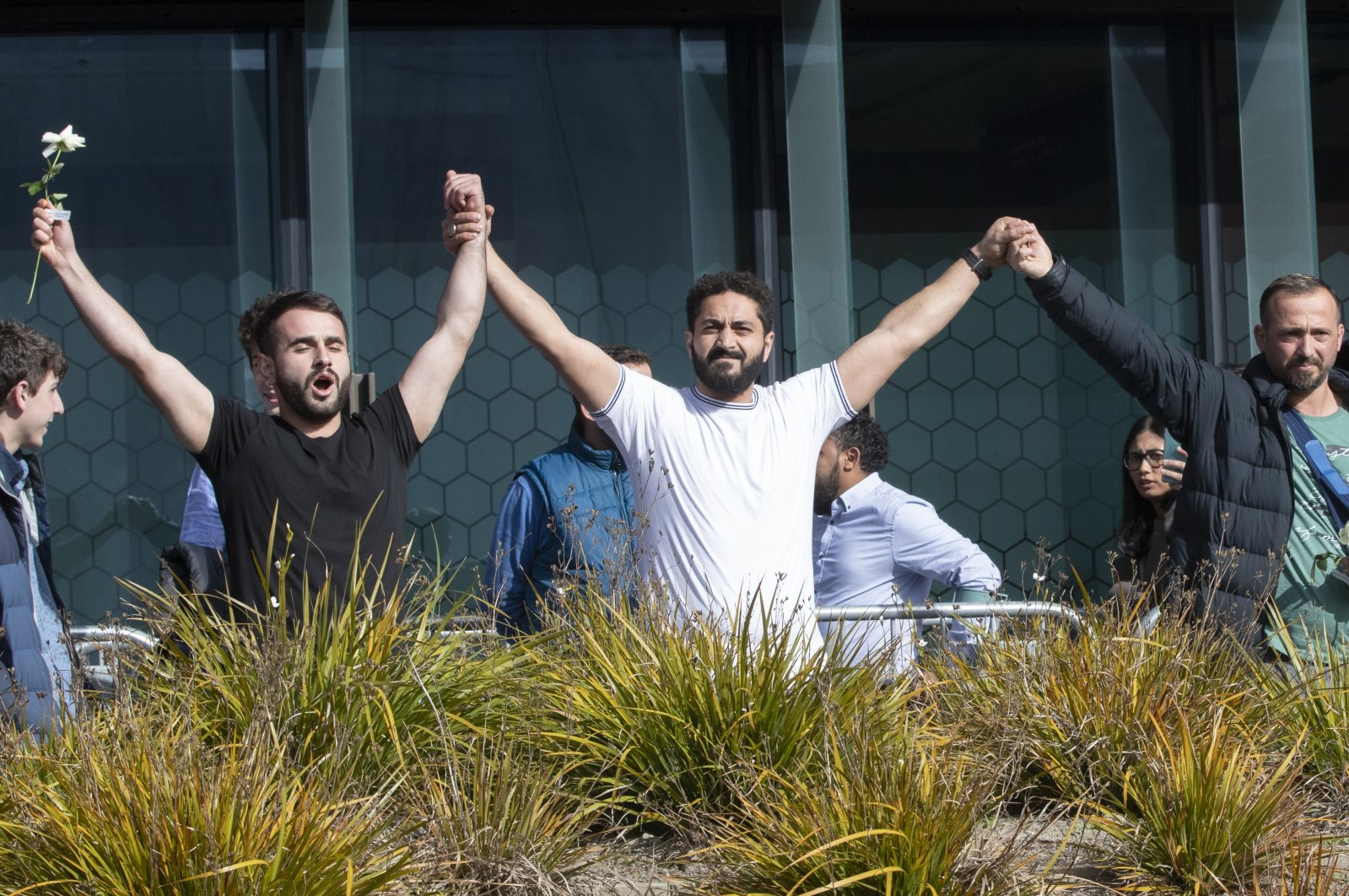 Mosque shooting survivors (L to R) Mustafa Boztaş, Wassail Daragmih and Temel Ataçocuğu celebrate as they leave the Christchurch High Court after the sentencing hearing for assailant Brenton Tarrant, in Christchurch, New Zealand, Aug. 27, 2020. (AP Photo)