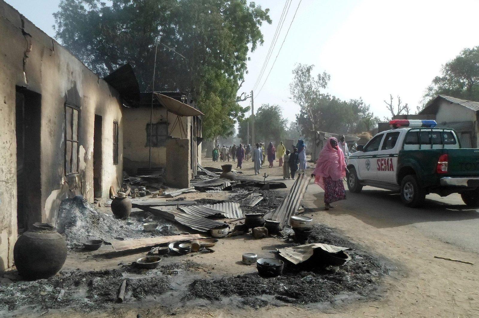 People walk past burnt houses after Boko Haram attacks in Dalori village on the outskirts of Maiduguri in northeastern Nigeria, Jan. 31, 2016. (AFP Photo)