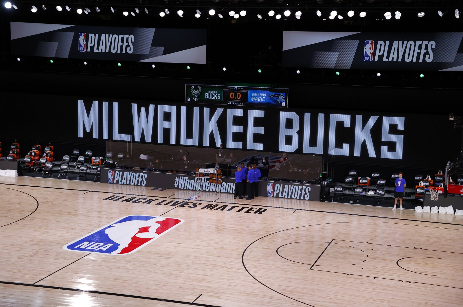 Referees huddle on an empty court at game time of a scheduled NBA playoff game between the Milwaukee Bucks and the Orlando Magic in Lake Buena Vista, Florida, U.S., Aug. 26, 2020. (AP Photo)