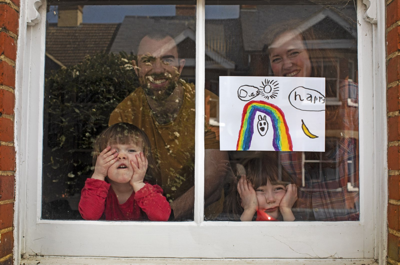 Amelie and her sister Camille look out from their front window as the coronavirus lockdown enters its third week, along with their parents, Victoria and Damian Kerr, in Berkhamsted, England, April 4, 2020. (AP Photo)