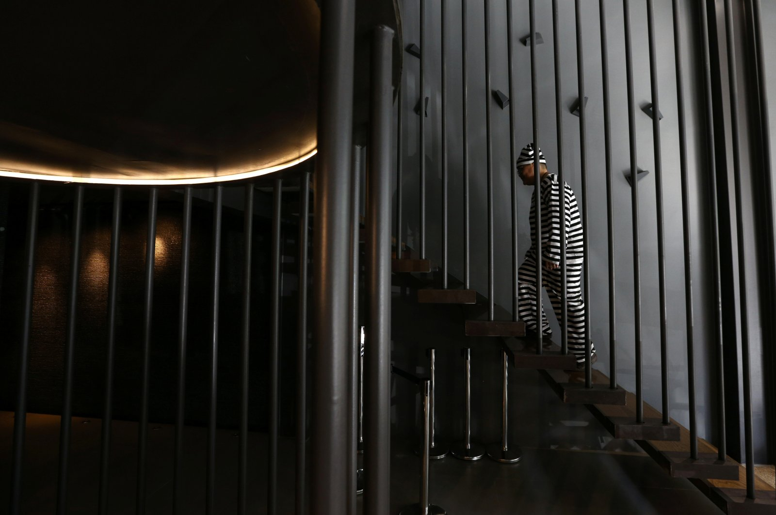 A hotel guest wearing prisoner uniform walks inside the Sook Station Bangkok's first prison-themed hostel, Thailand, Aug. 2, 2017. (Reuters Photo)