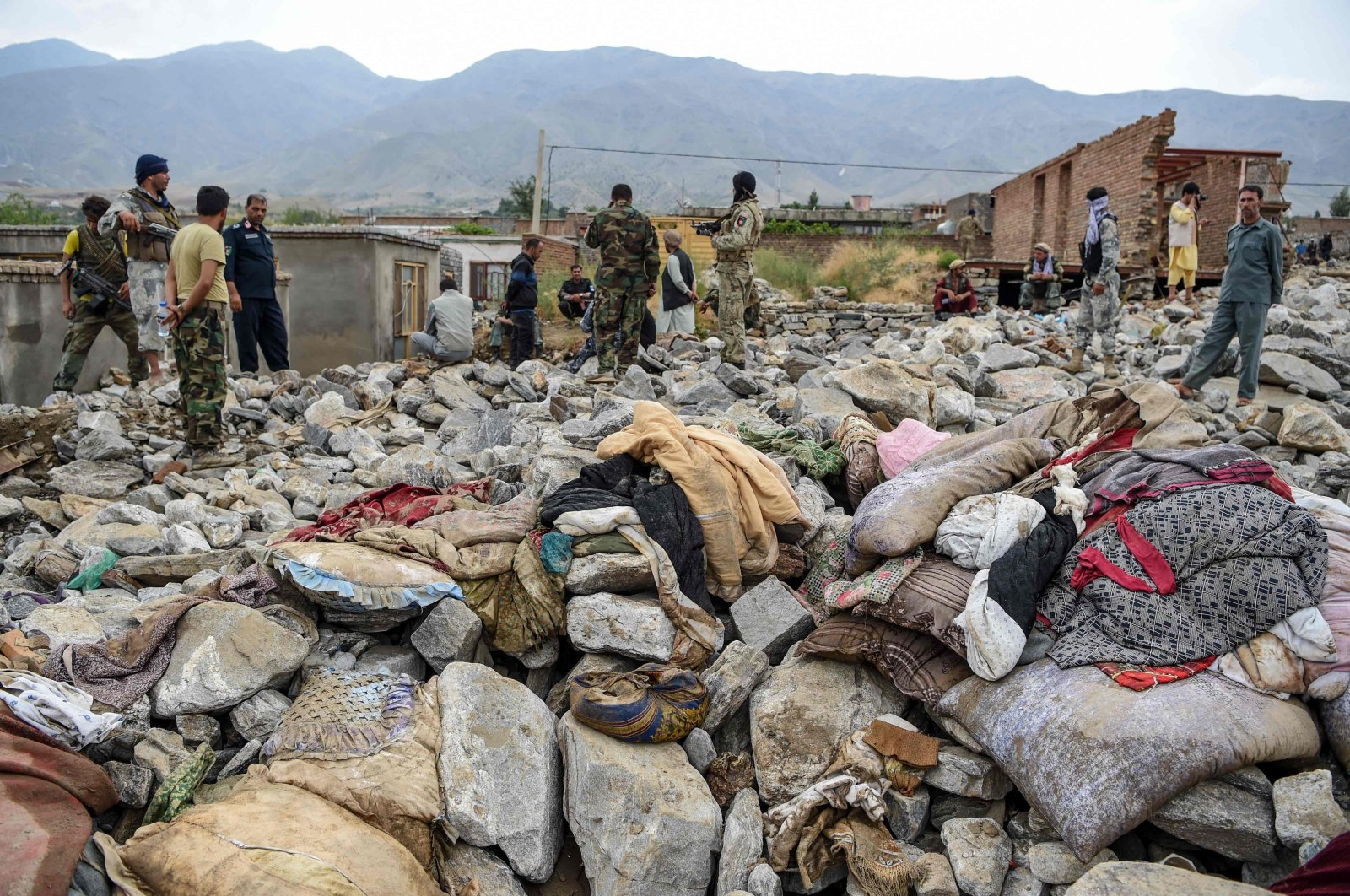 Villagers and security personnel gather after a flash flood affected the area at Sayrah-e-Hopiyan in Charikar, Parwan province, Afghanistan, Aug. 26, 2020. (AFP Photo)